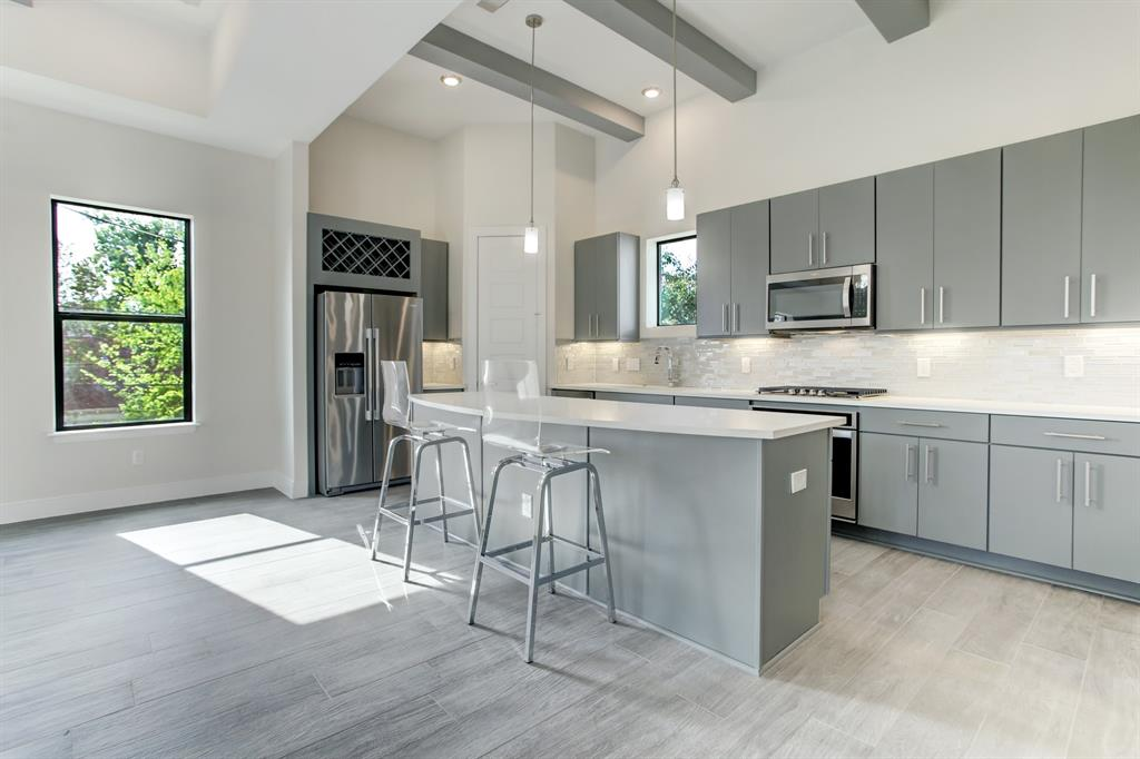 Kitchen features quartz countertops and island with breakfast bar