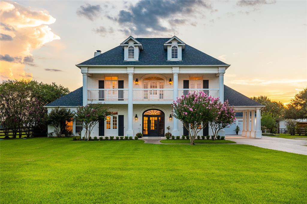 Stunning New Orleans Southern Colonial home in the quite equestrian community of Grand River. Situated on 5.95 acres (with an option to purchase approximately 13.5) of spectacularly manicured property within 35 minutes to downtown Houston! Perfectly situated on the grounds, this home has been tastefully designed with elegance for comfortable living and entertaining throughout. Rich hand-scraped maple hardwood floors, professional-grade Fisher and Paykel appliances, custom imported antique lighting, New Orleans style balcony's, gathering kitchen with a breakfast bar & island, and two custom staircases are just a few of the impressive details. Cool off in the refreshing pool framed by a grand pecan tree or enjoy the horse lovers dream with an outdoor arena, pastures, and a 36x40 barn equipped with 4/5 stalls and a charming tack room. Pack your boots and come enjoy the privacy of wide-open spaces in your new private estate!