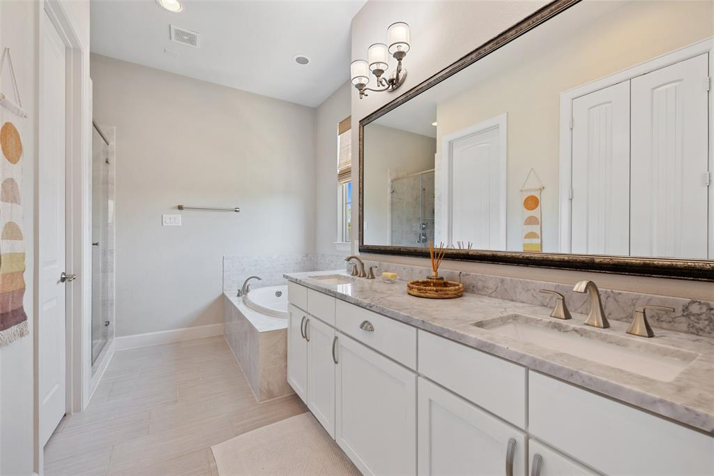 The spa-like master bathroom offers a large vanity, a giant soaking tub, and a separate shower.