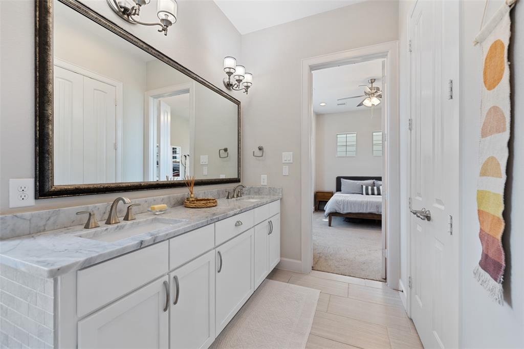 The primary bathroom vanity has great storage, a large decorative mirror, and 2 sinks.