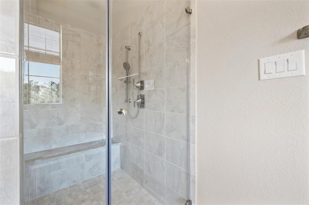 The frameless standup shower includes a bench and multi-jet shower.