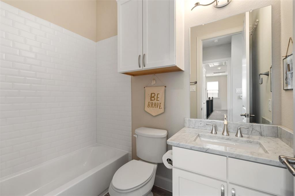 Another secondary bedroom en suite with gorgeous marble countertops and a subway tile bathtub surround.