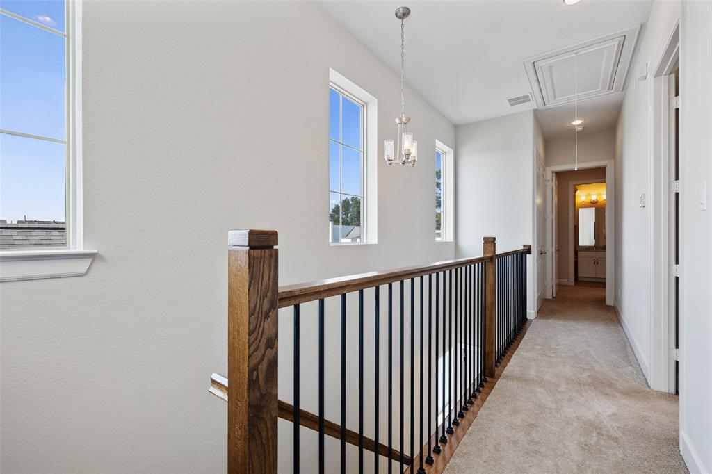 Even the main corridors of this home have tons of natural light and great touches like this iron and wood stair rail.