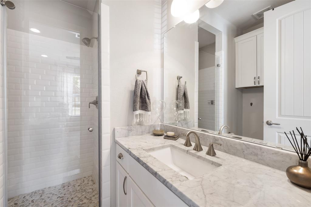 This gorgeous bathroom is located right off the downstairs bedroom. It has a beautiful shower with subway tile surround and pebble tile floor. The counter-tops are marble with an under counter sink.