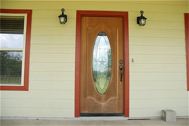Fresh Paint On Exterior Is Crisp Looking. Stained Wood Front Door Has Glass  Insert With Texas Star.
