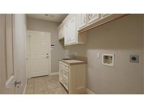 Large utility room with cabinets, storage and sink.