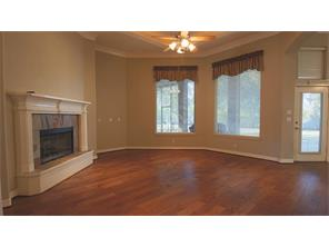 To the back of the home is the family room, with large gas fireplace includes glass front, gas logs, elegant mantle with tile front. Beautiful new wood floors.